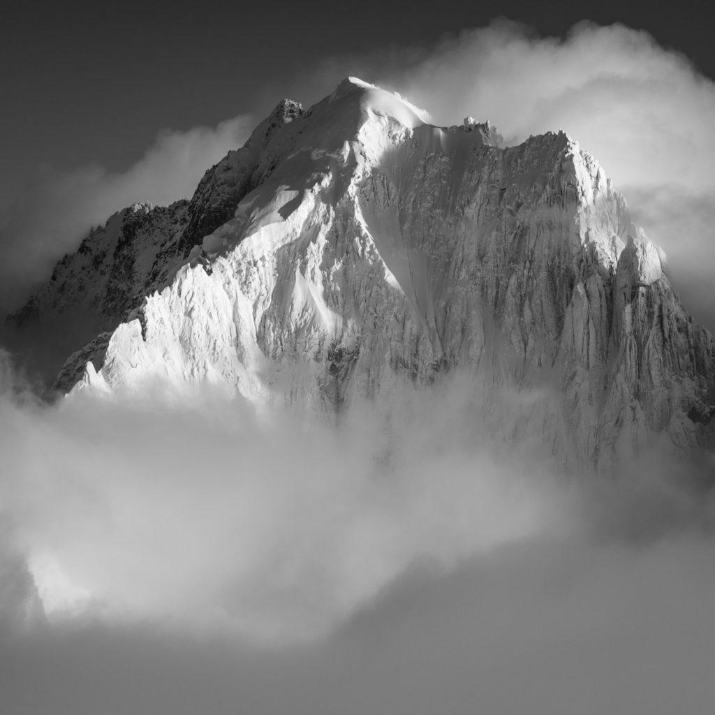 Photo noir et blanc de l'Aiguille Verte et des sommets des Alpes Chamonix dans les nuages et le brouillard après une tempête ed neige