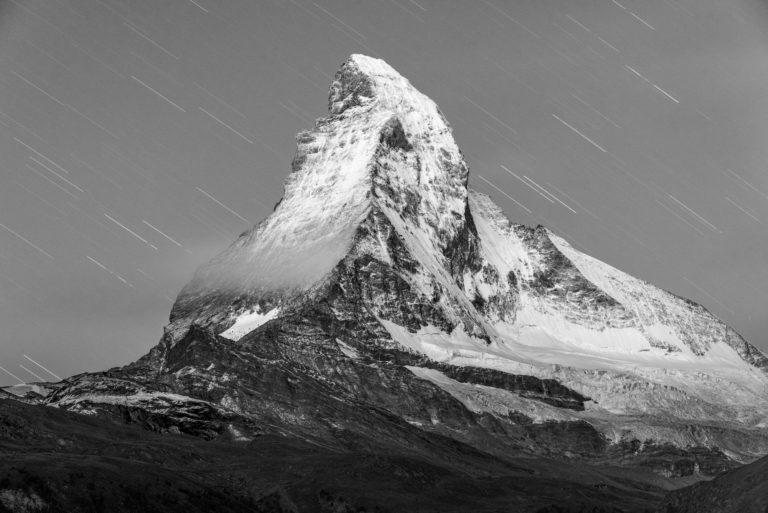 Pluie d'étoiles filantes sur le Mont Cervin - Photo de montagne la nuit en noir et blanc sur un sommet rocheux enneigé