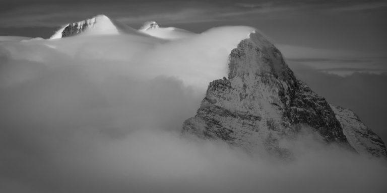 Eiger - Monch - Jungfrau - massif montagneux des somemts des Alpes en noir et blanc - arrête Mittellegi dans la brume