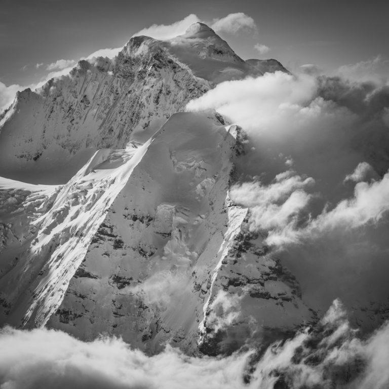 Jungfrau Suisse - le sommet de la montagne des Alpes Bernoises dans une fumée de nuages sous les rayons de soleil