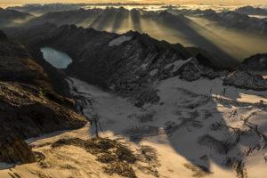 Panorama de montagne dans les Alpes Bernoises en Suisse - Vue aérienne en lever de soleil sur les montagnes rocheuses enneigées et d'un lac en montagne - Oberaar
