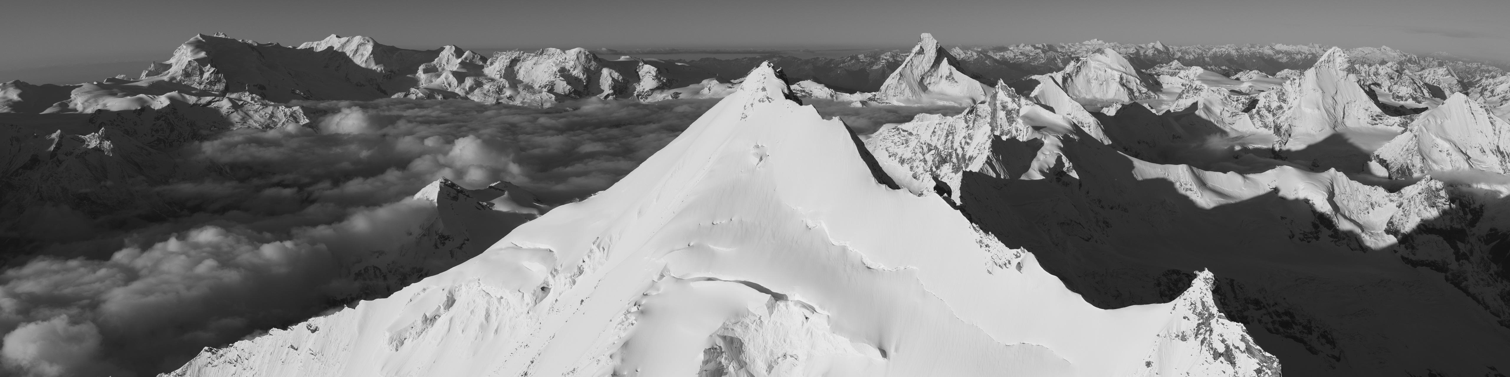 Photo panoramique noir et blanc d'une mer de nuage en montagne dans la vallée de Zermatt Val d'Anniviers