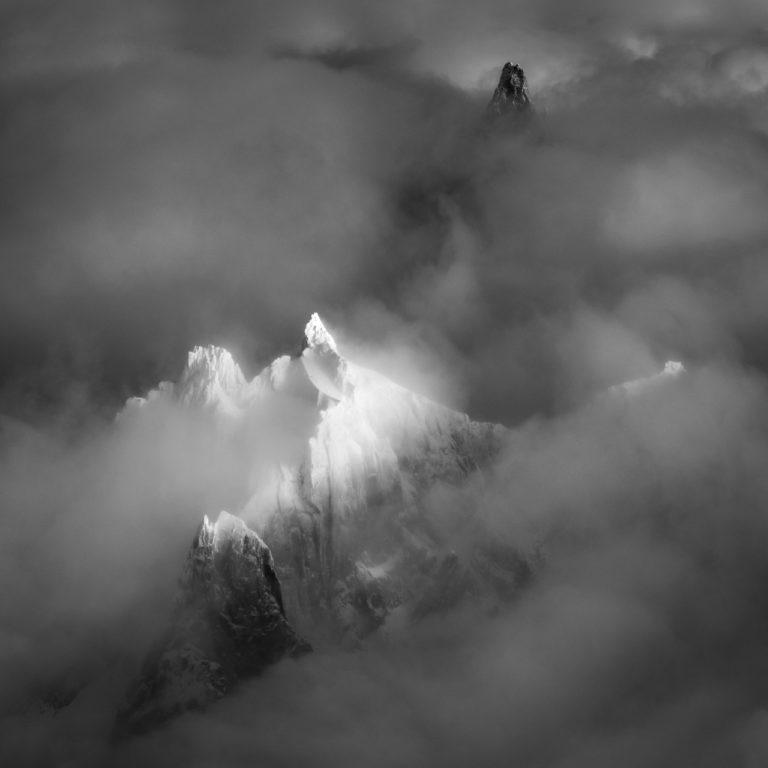 Massif du mont Blanc Chamonix en noir et blanc -Sommets des montagnes de l'Aiguille du Plan et de la Dent du Géant dans une mer de nuage et de brume brouillard