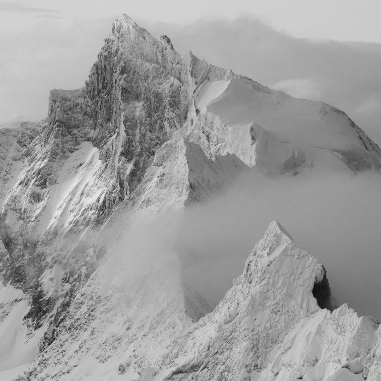 Image noir et blanc du Zinalrothorn et des sommets alpins suisses en noir et blanc dans la brouillard