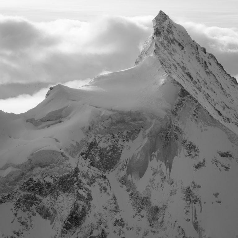 Photo noir et blanc de montagne enneigée et du Zinalrothorn depuis le Val d'Anniviers après une tempête de neige