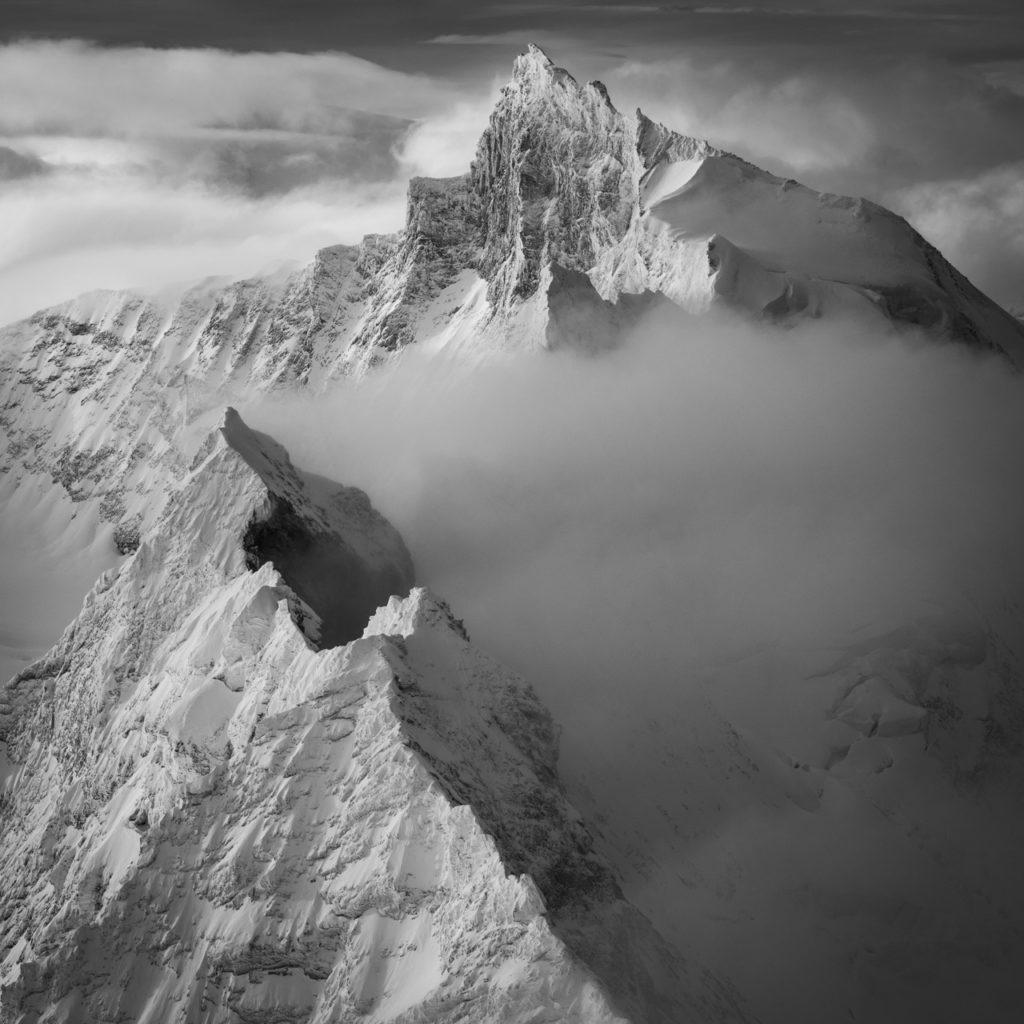 image montagne alpes noir et blanc dans une mer de nuages