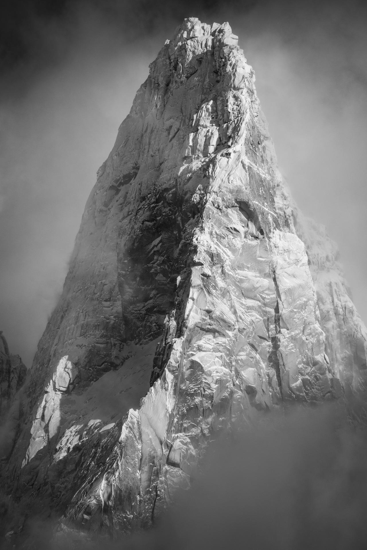 Photo noir et blanc des Drus Chamonix - Sommet des Drus après une tempète de neige qui sort de la mer de nuages