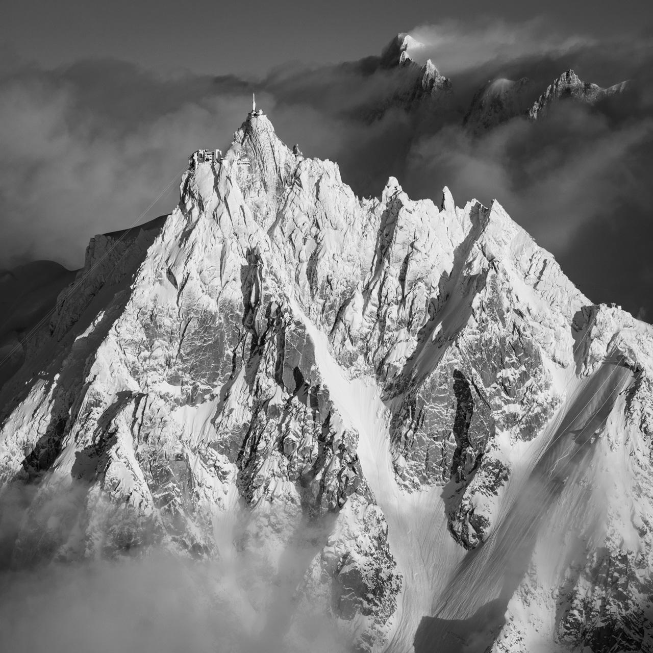 Photo de montagne de l'Aiguille du Midi - Chamonix vue aérienne - Montagne noir et banc- Télécabine de l'Aiguille du midi givrée